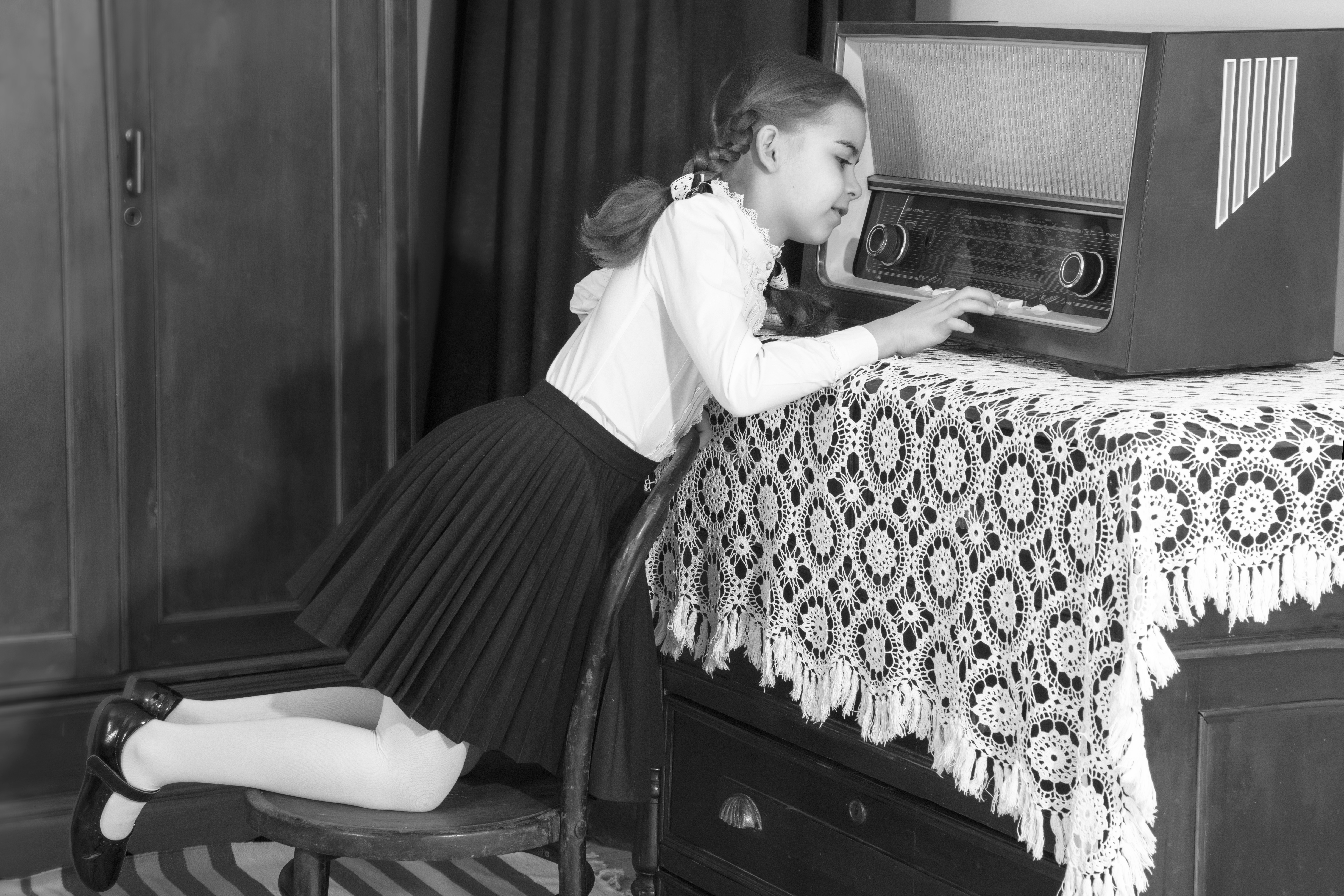 Black and white picture of a child playing with a radio