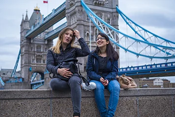 Two girls in front of the Tower Bridge in London