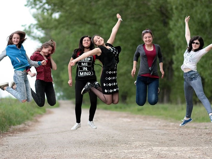 A group of girls jumping for a pose with forest in the background.