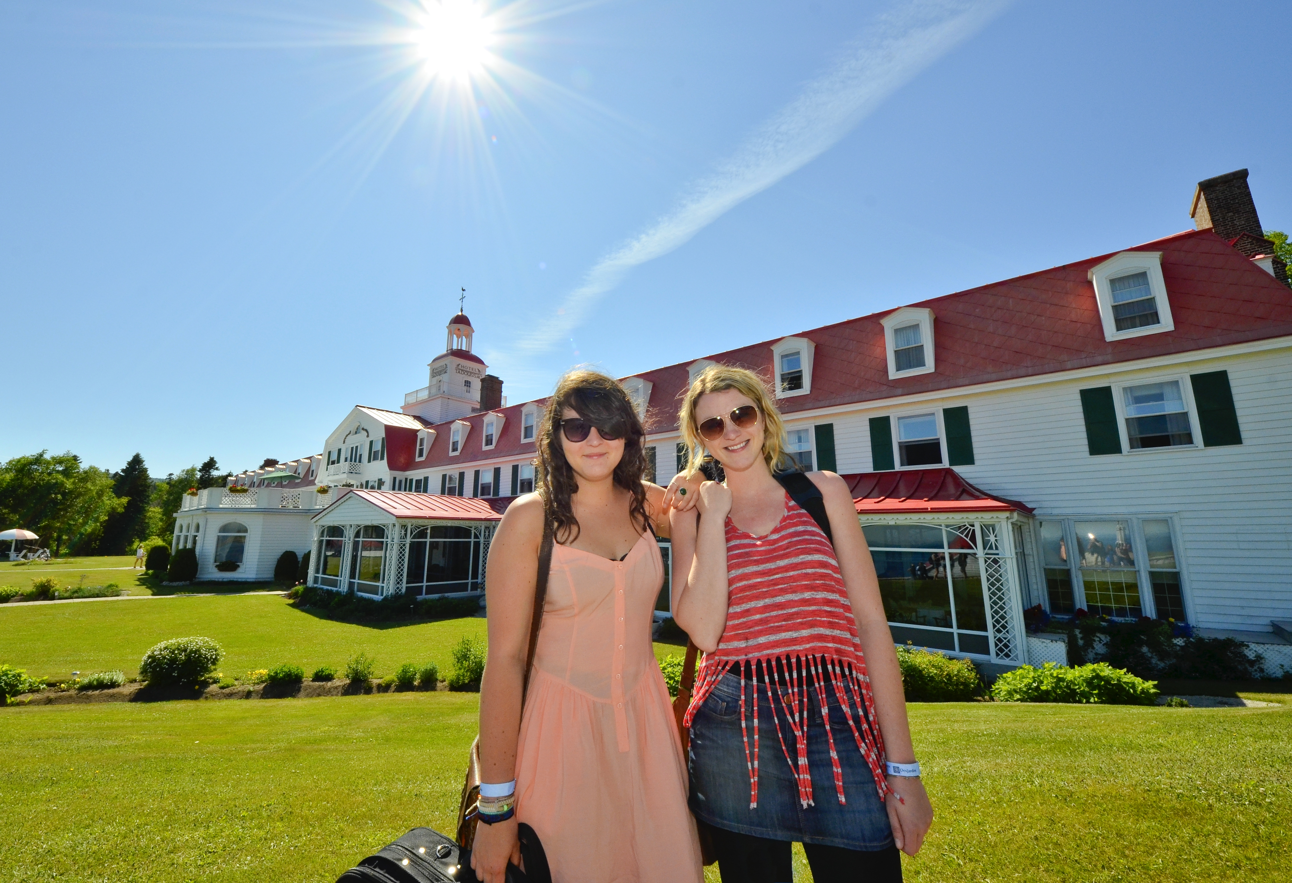 2 girls posing in front of Tadoussac Hotel.