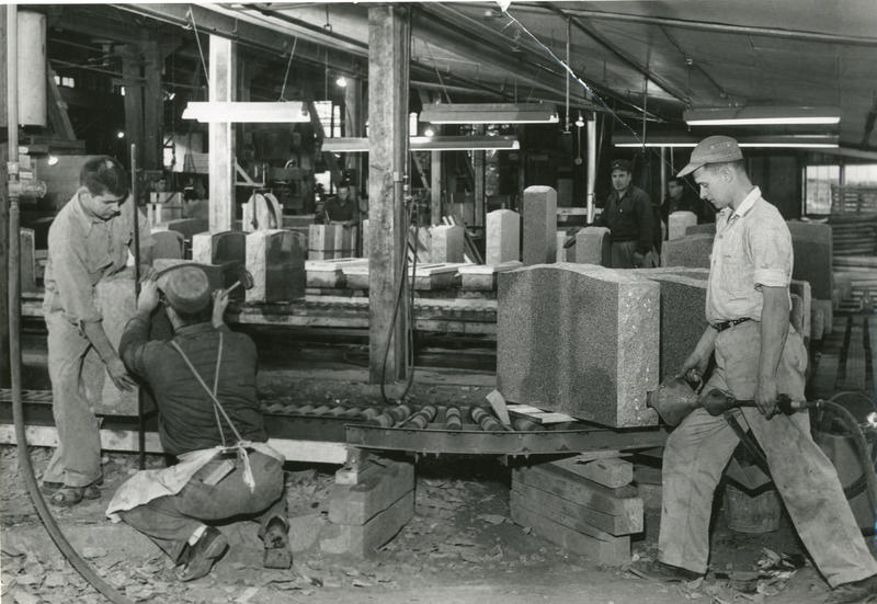 Black and white photography of men working in a factory.