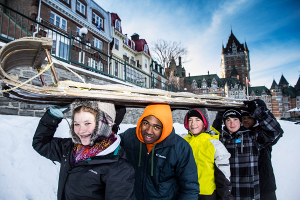 Students carrying a sled in Quebec winter setting.