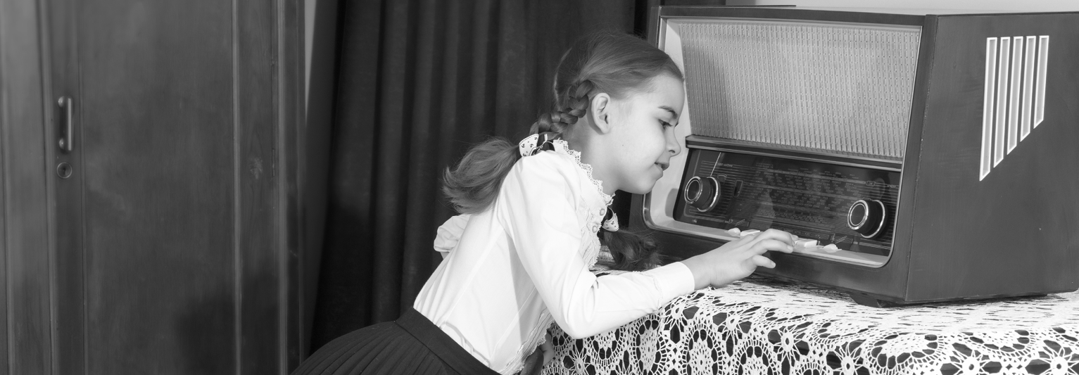 Black and white picture of a child playing with an AM radio